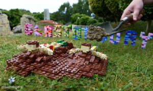 Model maker Hannah Reed places some real mud from Worth farm behind LEGO figures of Glastonbury mud sliders in the brand new Glastonbury Festival Miniland scene at Legoland, Windsor.